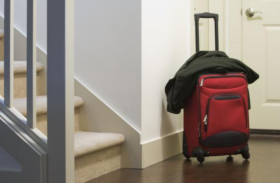 Suitcase and jacket in the foyer of a personal home