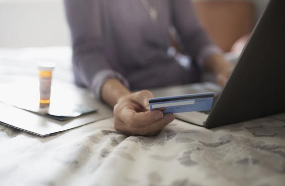 A woman holding a credit card while using a laptop
