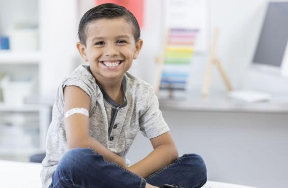 Young smiling boy in doctor's office with band-aid on his upper arm