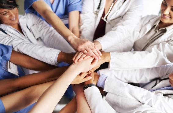 Nine medical professionals putting their hands together in the middle of a group circle