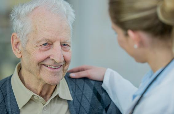 Older man smiling, comforted by doctor