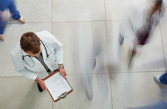 Physician looking at documents on a clipboard