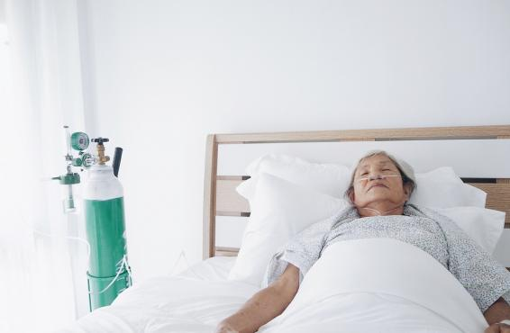 Woman in bed with an oxygen tank nearby