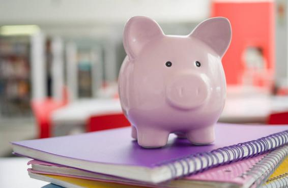 Piggy bank on top of some notebooks