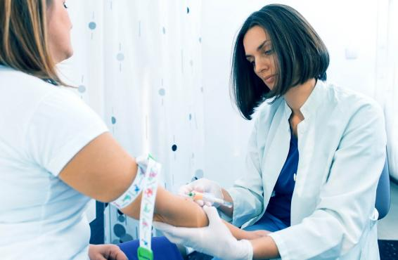 Female doctor taking blood sample from female patient