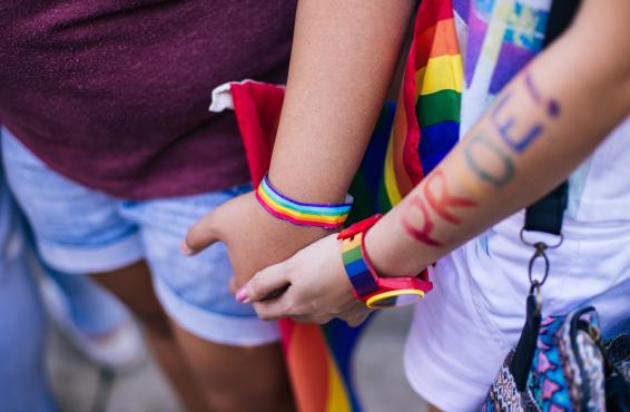 "People holding hands with pride bracelets on wrists and""pride"" written on arm."