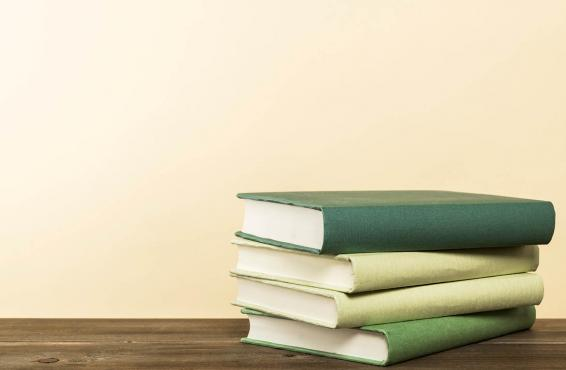 Stack of green books on wooden table.
