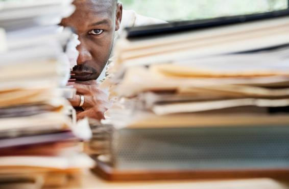 Man staring at a large stack of papers