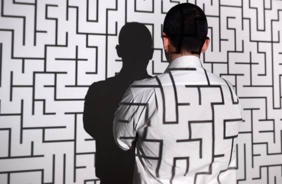 Projection of a maze on wall and man