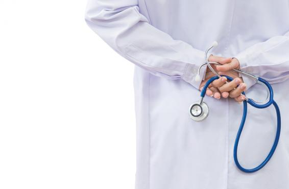 Physician holding stethoscope behind back