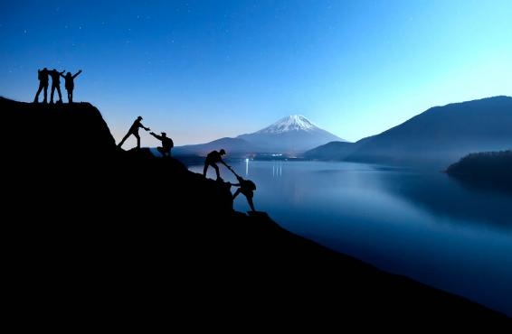 Silhouette of team climbing a mountain