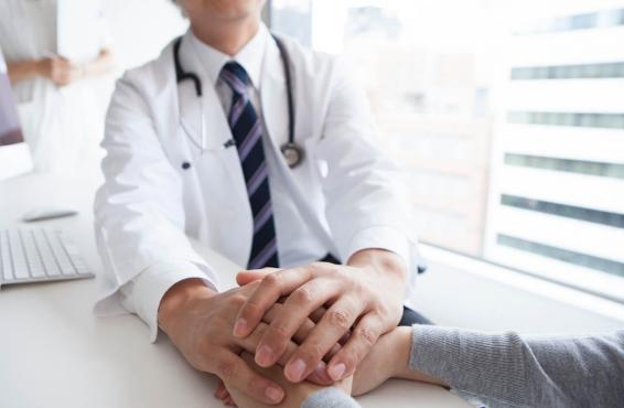 Physician and patient holding hands