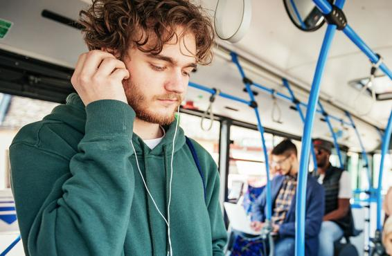 Young man with headphones on the bus