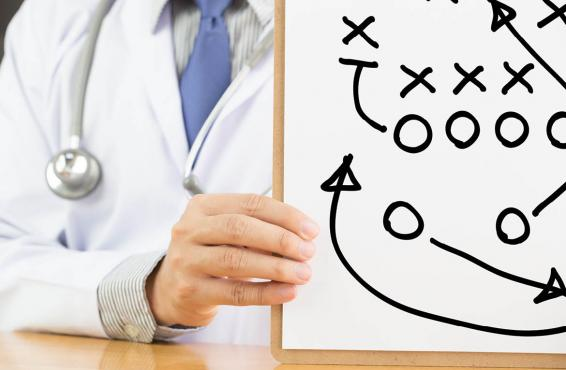"Physician holding a white board with x and o ""game plan"" drawing"