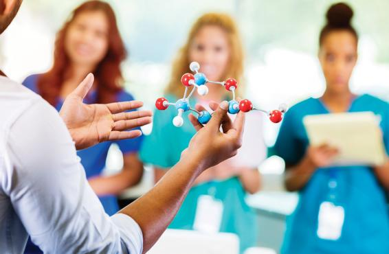 Man holding an atom model to teach residents