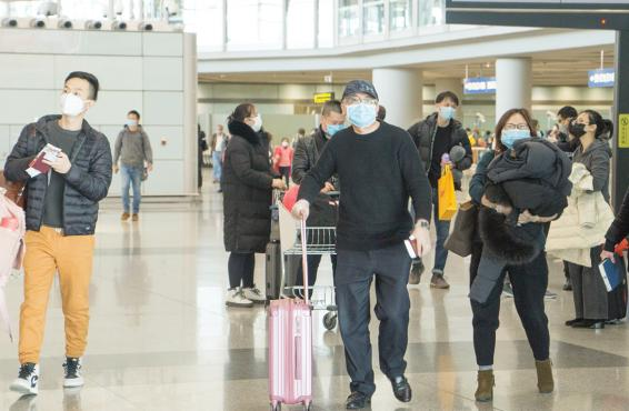 Travelers in an airport wearing face masks