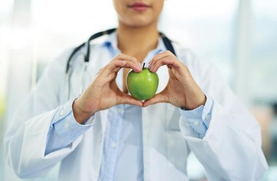 Physician holding a green apple