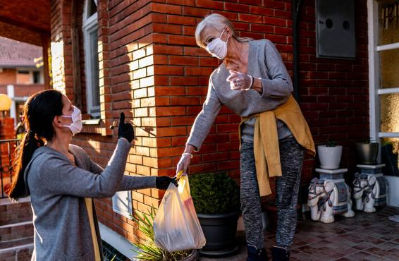 Woman handing groceries to another woman