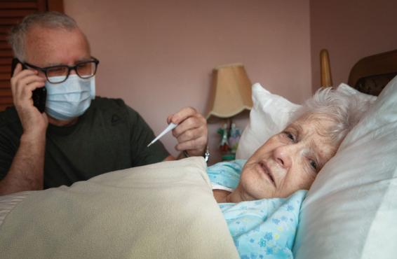 Man with thermometer sitting next to woman lying in bed