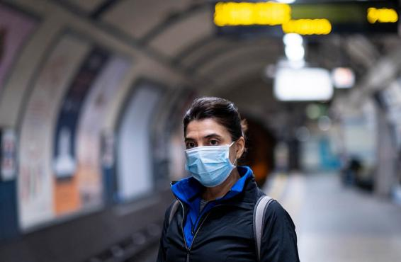 Person wearing facemask in an empty underground train station