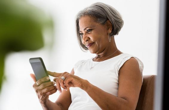 Woman staring down at mobile device.