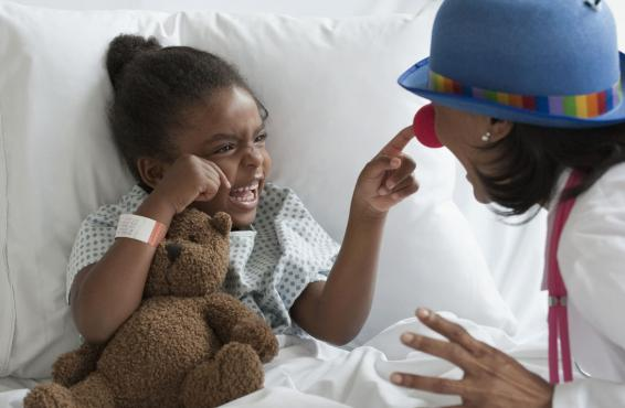 Young smiling patient pointing at a clown's nose