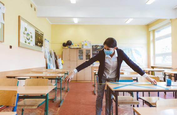 Person in face mask preparing a classroom