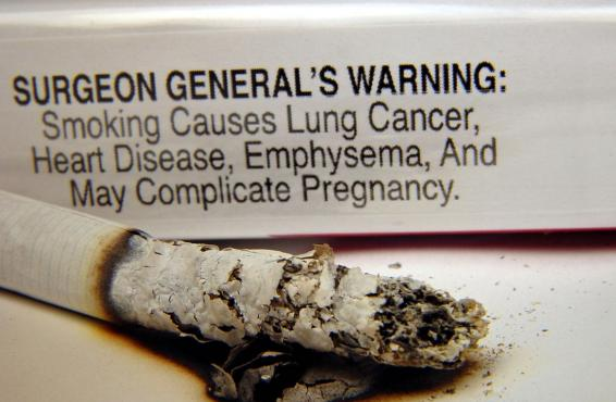 Close-up of a burning cigarette and cigarette pack text-only warning label