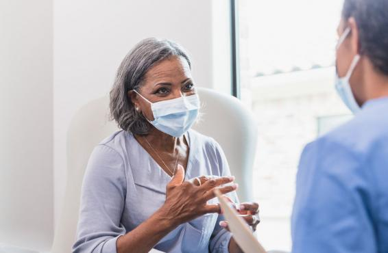 Patient talking to a doctor, both wearing masks.