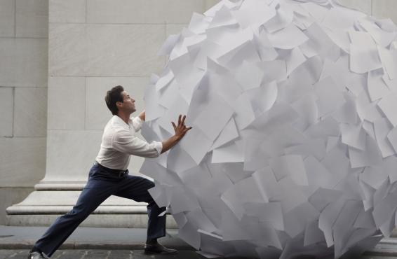 Person rolling a large ball of paper down a street