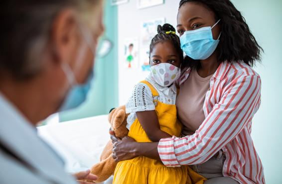 A doctor speaking to an African-American mother and her child, all of them wearing masks.