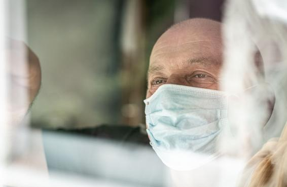 Person wearing a face mask and looking out a window