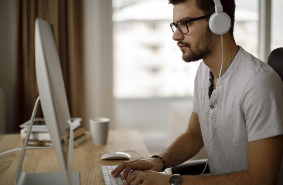 Man wearing glasses and headphones typing at a desktop computer.