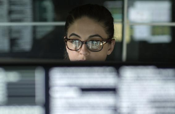 Woman in glasses working at a computer in a darkened room with blurred computer monitors in the foreground.