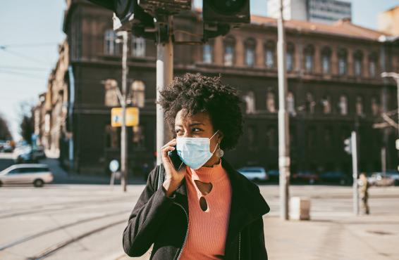 Woman walking down the street wearing a face mask and talking on a cell phone.