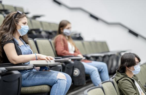 Three students sitting in an auditorium wearing masks and distanced from each other.