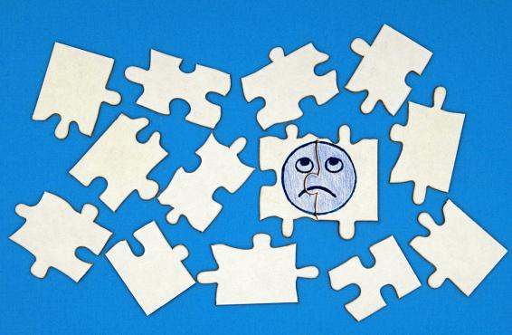 Jigsaw puzzle pieces with sad emoji face.