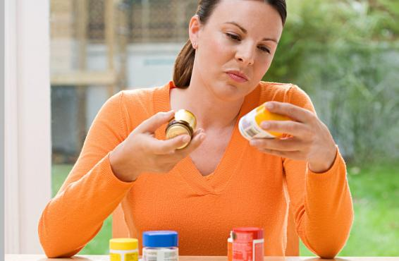 Woman choosing between supplements