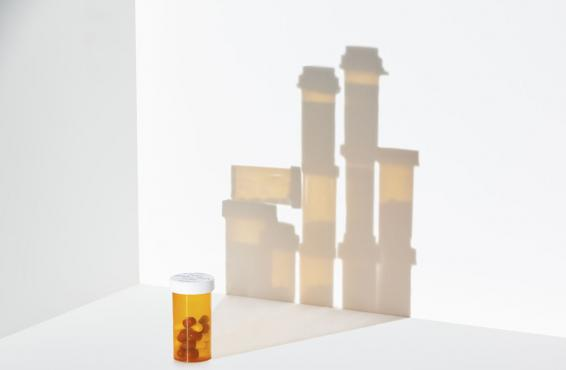 Bottle of pills in foregroud with background of more bottles in shadow