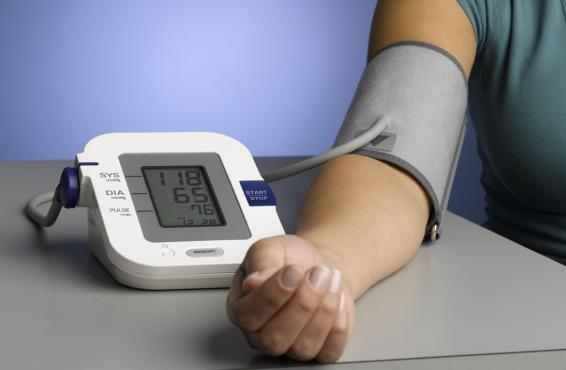 Person using an upper arm blood pressure monitor and cuff_Tight shot