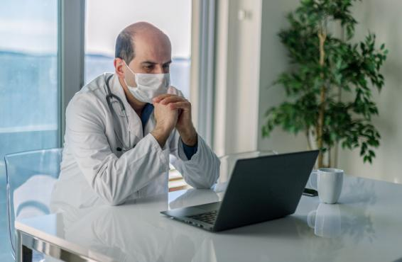 Physician wearing a mask and sitting at a desk looking at laptop screen