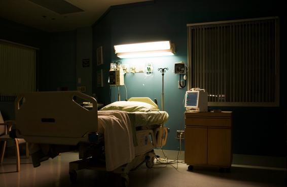 Empty hospital bed at night lit from above.