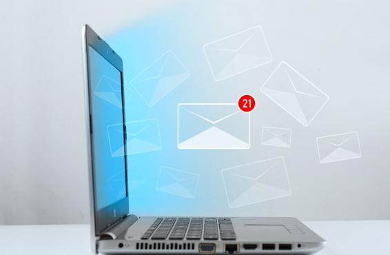 Photo-illustration of an email icon, a white envelop with a red 21 notification, hovering above an open laptop.