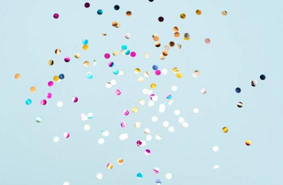 Different colors of confetti against a blue background.