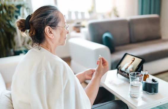 Woman with medicine in her hand talking to her doctor during a telehealth appointment.