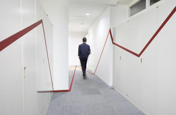 Person in blue suit walking down empty hallway and walls with a red stripe on each side.
