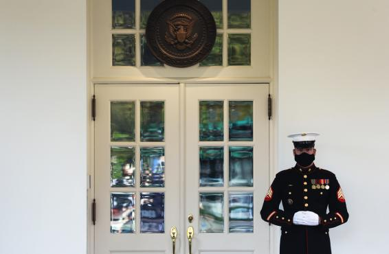 A U.S. Marine stands guard outside the West Wing at the White House
