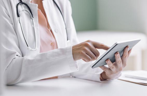 Close-up of a physician using a smart tablet.