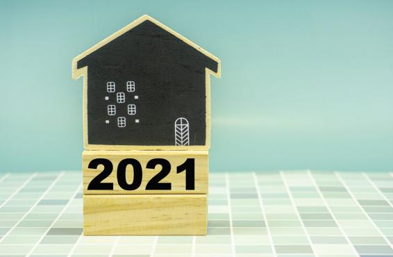 A house made of wooden blocks with one block labeled '2021' on a white and light blue tiled surface.