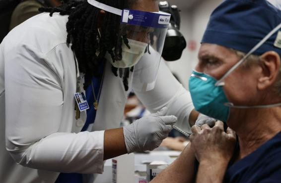 A health care worker in PPE giving a vaccination to a physician in a mask.
